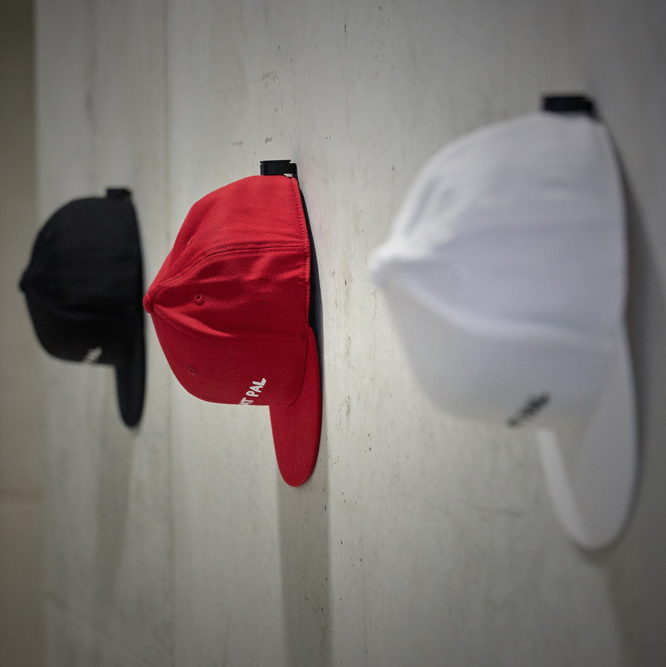snapback on wall mounted cap hanger by the hat pal.