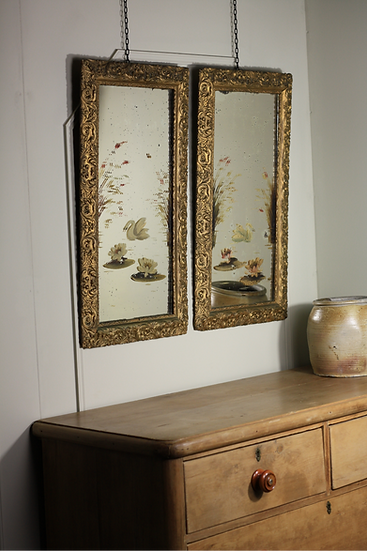 A pair of gilt framed painted mirrors