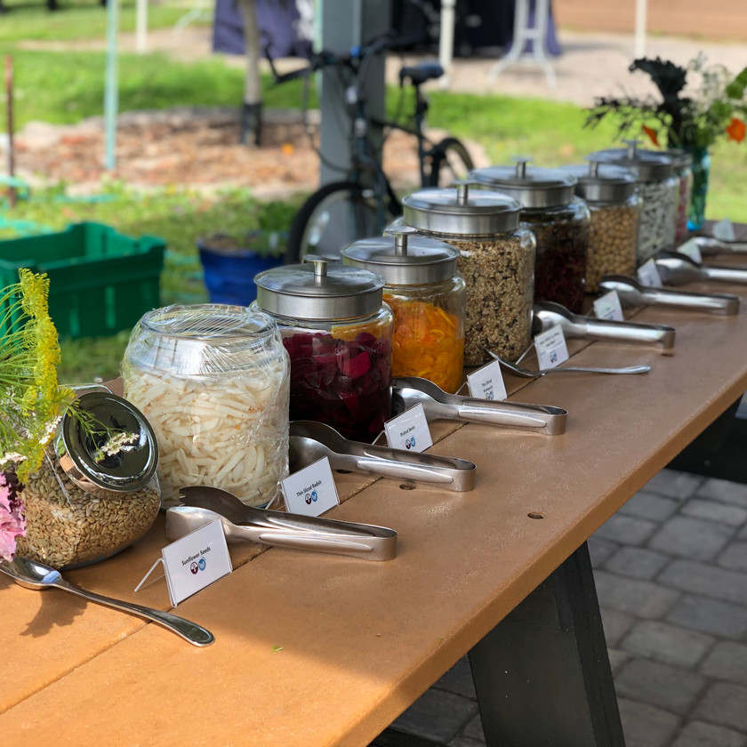 There is a row of large jars filled with salad toppings. There are tongs next to each jar and this is located in the Ogier Gardens. This is what the Pick Your Own Salad event looked like in previous years.