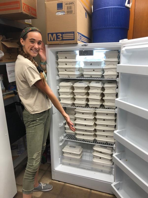 UNF student volunteer standing in front of a fridge packed full of meals that were packaged at the Food Fighters food recovery. These meals are available for pick up in this facility which is the Northeast Florida Aids Network.