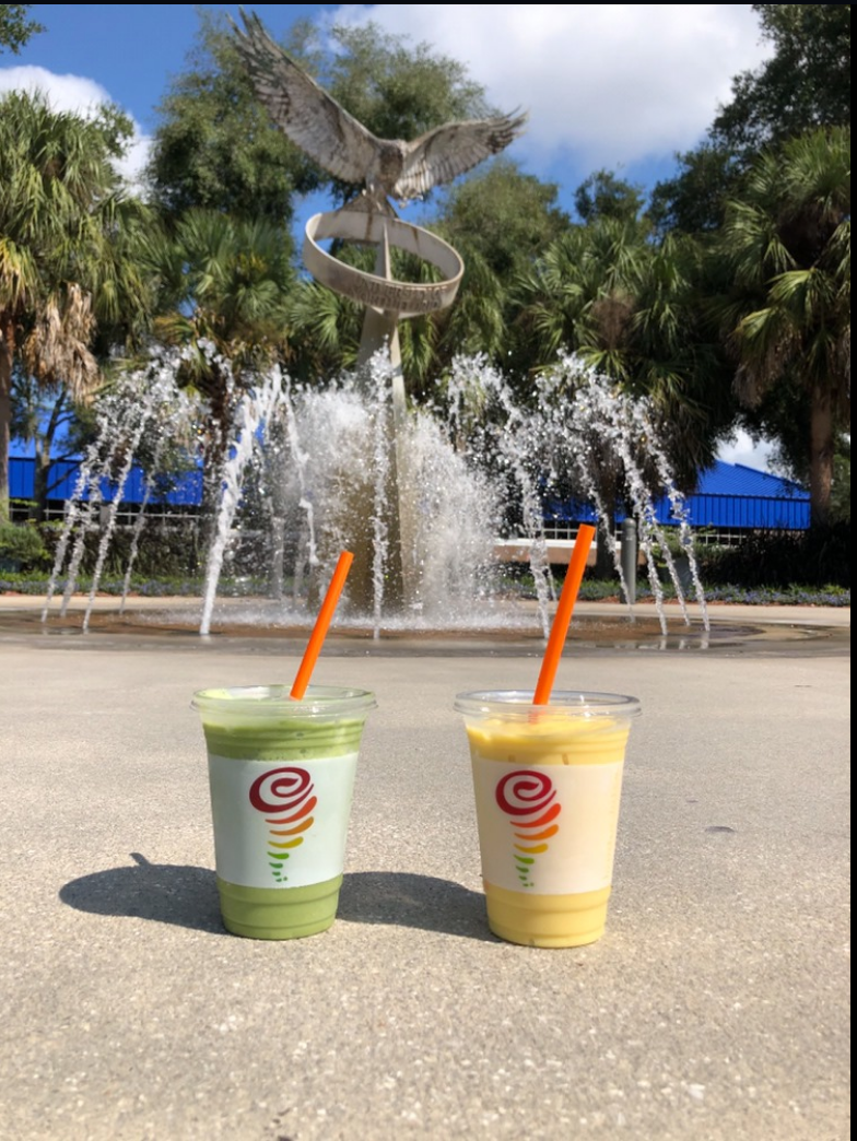 There is a green and yellow smoothies from UNF's Jamba Juice located on the ground next to each other. The are positioned in front of the Osprey Fountain that is located in front of the basketball arena.
