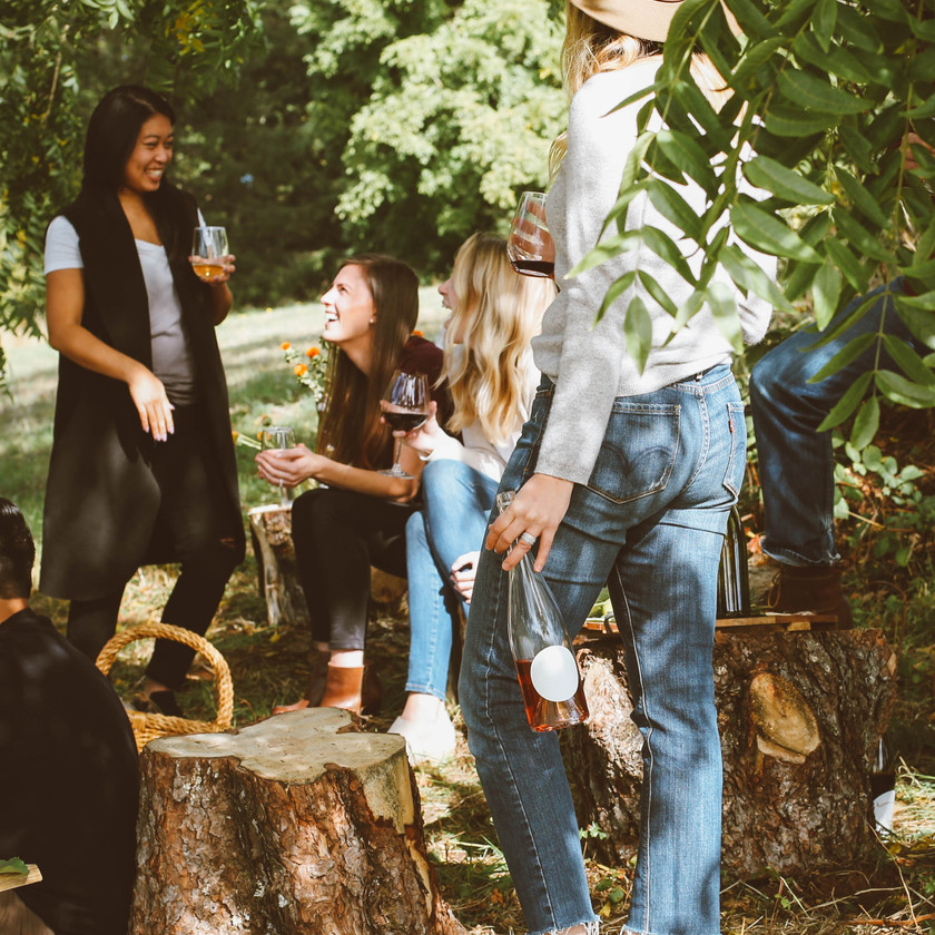 Group of girls standing outside chatting. The girls are holding beverages and seem to be happy and enjoying the beautiful weather. They are surrounded by greenery.