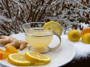 Cup of yellow tea with a lemon wedge on the rim sitting on a plate with a ginger root, orange slices, and lemon slices. The mug is outside in a wintery-scene with snow and branches in the background.