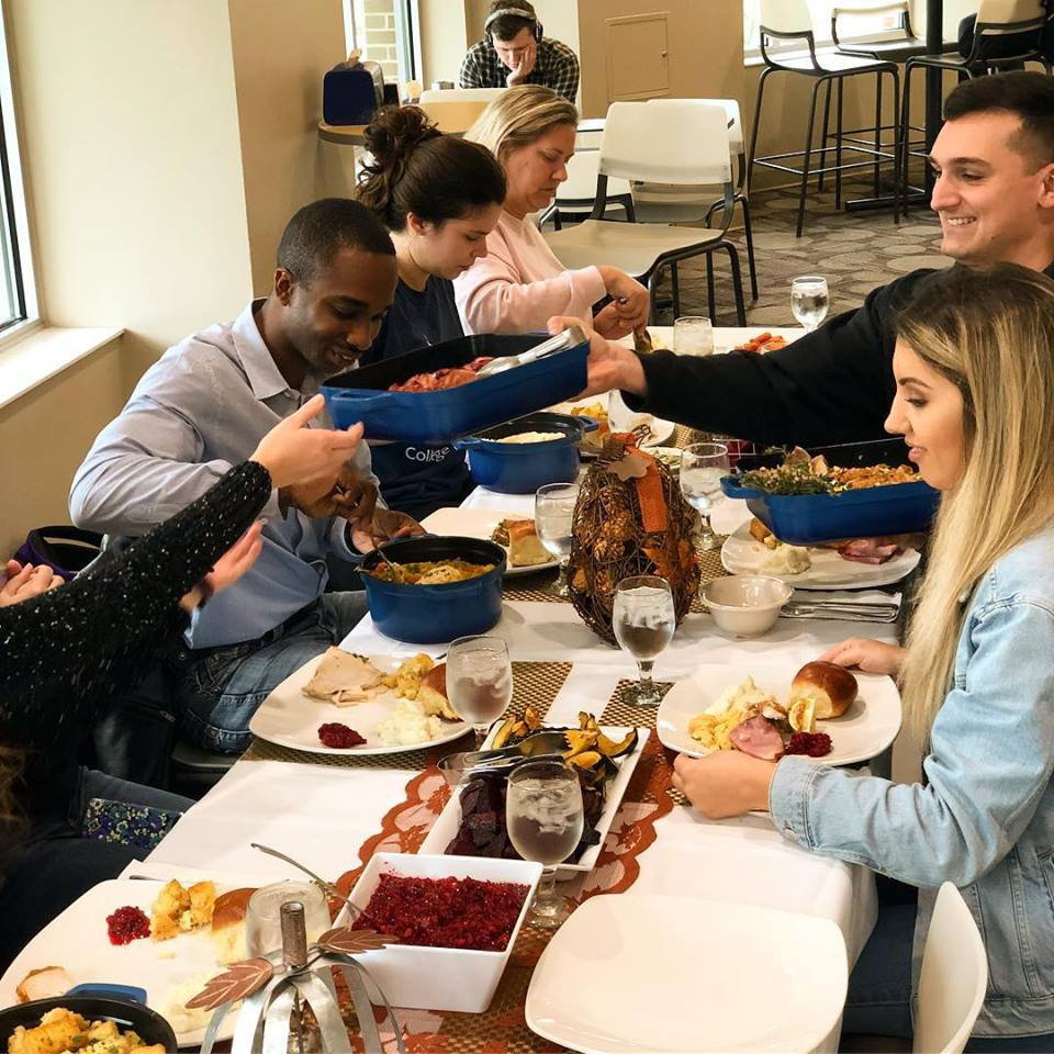 Photo is of students sitting at the Friendsgiving table last year. Students are passing around dishes and scooping food onto their plate while chatting with one another.