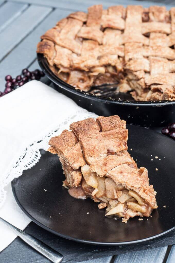 The vegan apple pie is cut into a single piece. The weaving top layers are perfectly browned.