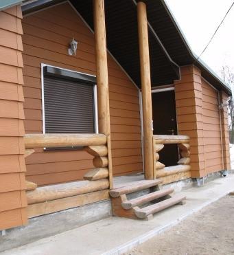 Строганные и деревянные доски прибитые к стене дома - сайдинг