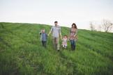Happy Family Walking in a Field - Family photographers in Dubai