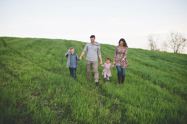 Young family walking on a grassy hill, mom, dad, son, daughter