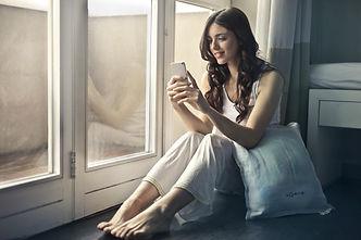 woman-sitting-beside-window-holding-phon