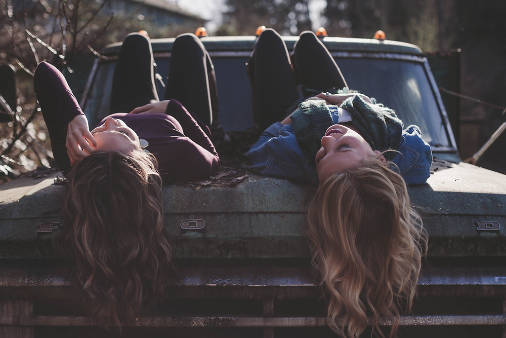 Two teenage girls lie on the hood of a car talking.