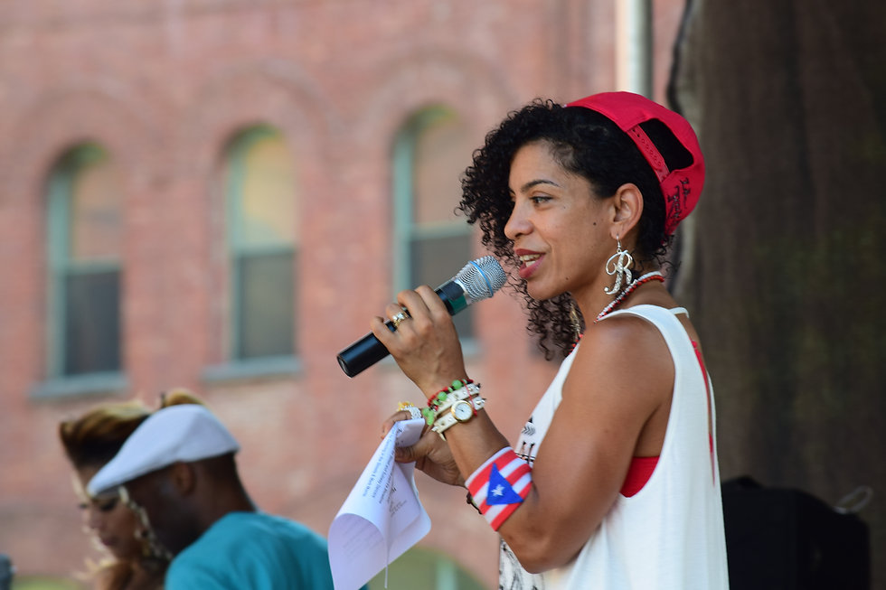 Hispanic woman with microphone speaking to a community in the Bronx