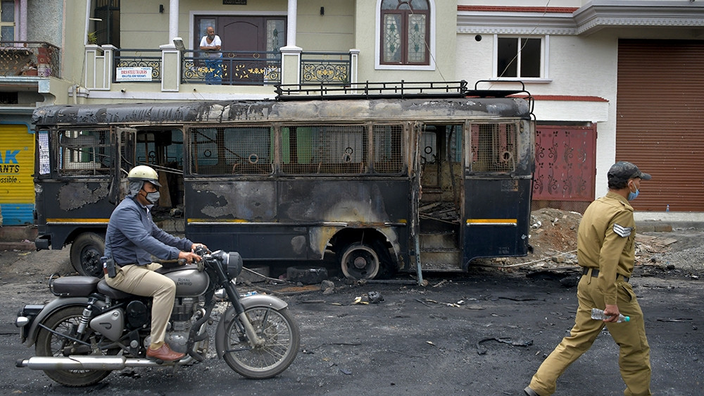 A policeman rides past a burned police vehicle in Bengaluru on August 12 after violence broke out following a 'derogatory' Facebook post about the Prophet Mohammed [Manjunath Kiran/AFP]