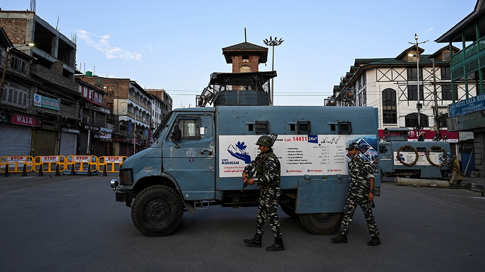 Paramilitary soldiers guard at a checkpoint during a curfew in Srinagar on August 4 [Tauseef Mustafa/AFP]