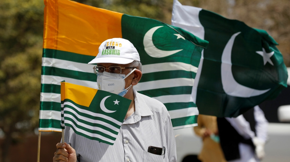 A man in Pakistani city of Karachi holds a flag as he observes a one-minute silence with others to mark the 'Day of Exploitation in Kashmir', one year after the Indian government stripped Kashmir of its autonomy [Akhtar Soomro/Reuters]