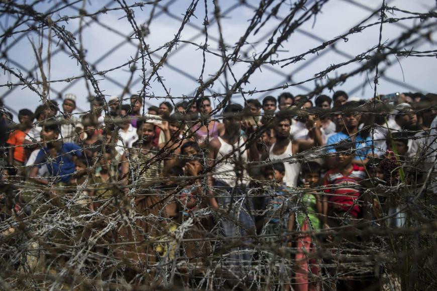 "Rohingya refugees gather behind a barbed-wire fence in the ""no-man's land"" border zone between Myanmar and Bangladesh, April 25, 2018. © 2018 Ye Aung Thu/AFP/Getty Images"