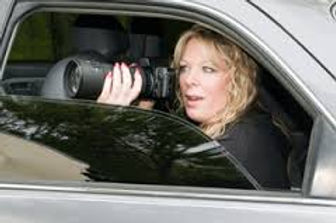 A female Private Investigator sits in her car with windows half down and holding a camera taking a picture.