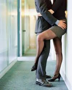 A lady and a man embrace in a hallway and she wraps a leg around the back of his leg.