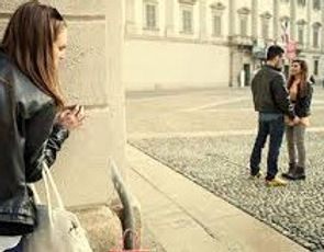 A Girl peeks around a wall spying on her boyfriend as he's talking to another girl and their holding hands.