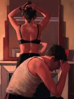 A women getting dressed in front of mirror while man sits on the side of the bed with his head in his hands.