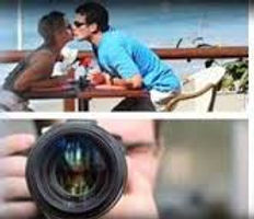 A man and women reach for a kiss across a taBLE IN THE UPPER IMAGE AND a man with a camera taking the picture.