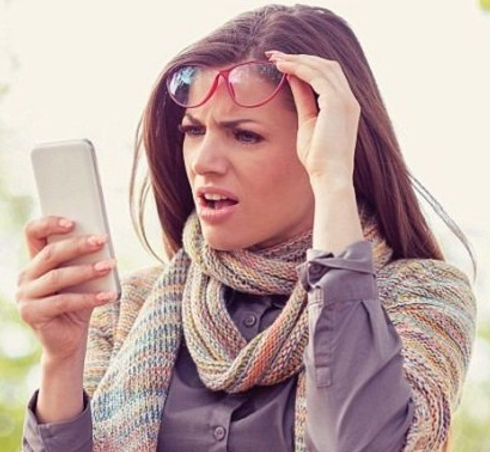 A women looking at her phone takes off her glasses to look closer at surprising text.
