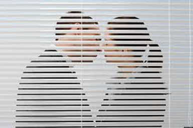 looking through a window with blind slightly open you can see a man and a women about to kiss.