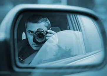 A male Private Investigator sits in his car with the window rolled down halfway, holding a camera and taking a picture.
