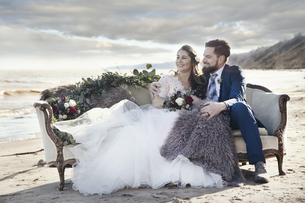 A married couple sitting on a sofa for their wedding photography