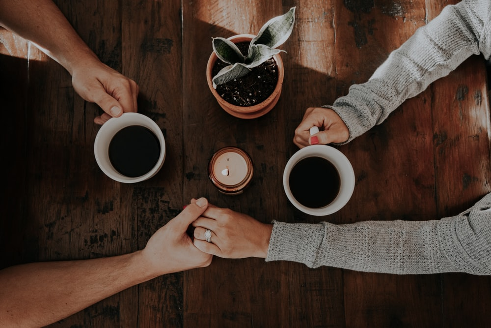 A couple holding each other's hands while having coffee on a wooden table