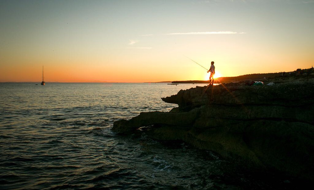Fisherman on the beach/rocks while the sun is setting in Menorca, taken by IDEAlee