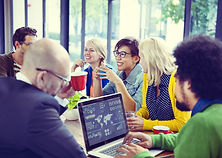 オフィスチームがドリンク片手にミーティング。笑顔があって楽しそうな雰囲気。
