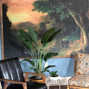 close up image of 2 vintage chairs, one black leather and the other colorfully patterned with tall plant and mural of a landscape of the woods in the background