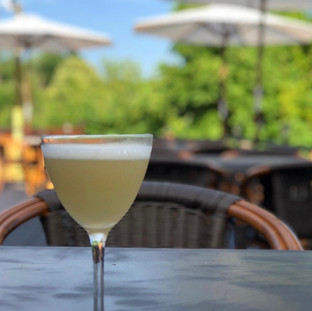 light yellow colored cocktail with a frothy top on outdoor dining table with umbrellas and trees in the background