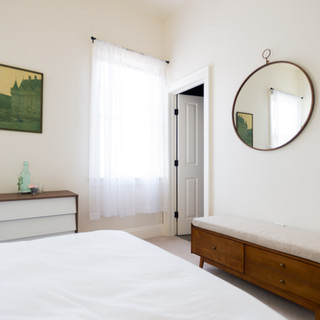 photo of a guestroom showing a portion of the bed, covered in white bedding. Also in the room is an oversized round mirror. Under this is mid-century modern cushioned bench with drawers.  On another wall sits a white and wood dresser, with a painiting of a castle in green tones hanging above it.  On the dresser is a bottle of water. There is a window with bright sunlight and sheer white curtains. To the right of the window is an open door.