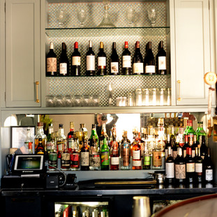 light blue-grey back bar cabinetry with neatly arranged liquor and wine bottles and crystal glassware