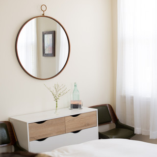 guestroom detail photo showing oversized round mirror hanging over mid-century modern white and natural wood dresser. Sheer white curtains hang in the window and 2 vintage green chairs are on either side of the dresser