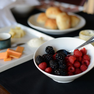 fresh blackberries and raspberries in a white bowl with a cheese plate and biscuits in the background