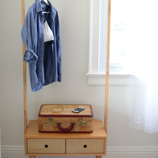 detail photo of sunny guestroom with a blonde wood mid-century modern inspired coatrack with bench containing 2 small drawers.  Hanging on the rack is a blue button-down shirt and on the bench sits a tan, vintage suitcase