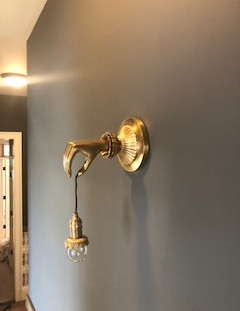 close up image of hallway brass sconce, which is a Victorian lady's hand holding a dangling lightbulb