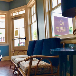image of rattan couch with both dark and colorful cushions and in the background are windows outside of which the store sign can be viewed.  The sign is large, square, stained wood reading the words Vanderbilt Lakeside Bar Room and Guesthouse
