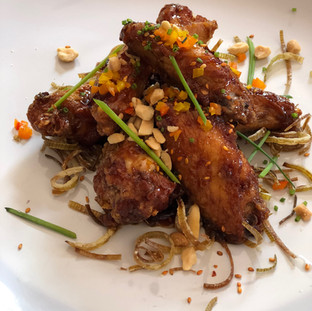 chicken wings in sweet and sticky sauce with crushed peanuts on top