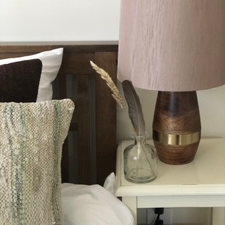 close up image of guest room showing turkish pillows, mid century modern wood lamp and small glass vase with a feather in it on white end table