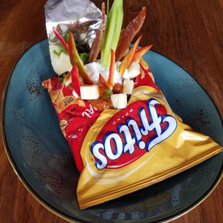 a bag of Frito brand chips cut open and filled with chili, cheddar cubes, and fresh peppers