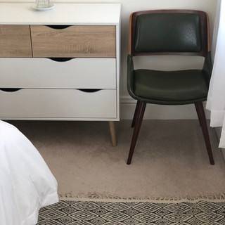 detail image of guestroom with mid-century modern green chair and white and wood dresser and portion of graphic black and white rug