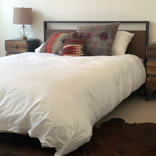 close up of a guestroom with queen sized bed covered in plush white comforter, turkish pillows and on the floor is a brown cow hide rug on top of cream colored carpet