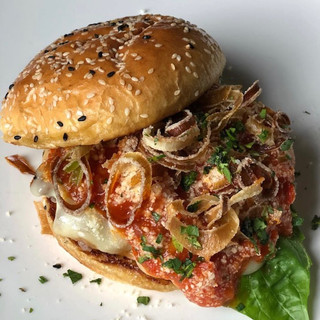 image of a cheesburger with seseme seed bun topped with fried jalapeno peppers and basil