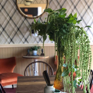 abundant green fresh cut flower arrangement on table with plaid wallpaper and orange chairs in the background