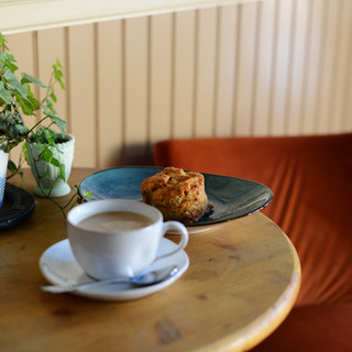 cup of coffee, cheddar biscuit, green plant on a round wooden table with orange colored velvet chair in the background