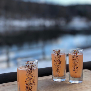 close up image of 3 shot glasses filled with a pink drink and down one side of each glass is chili salt.  Snow covered trees and lake in background
