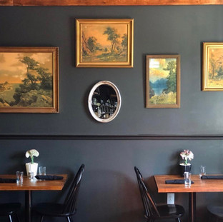 2 wood finished dining tables with black chairs, side by side against wall painted black with 4 landscape paintings arranged asymetrically and a small oval mirror